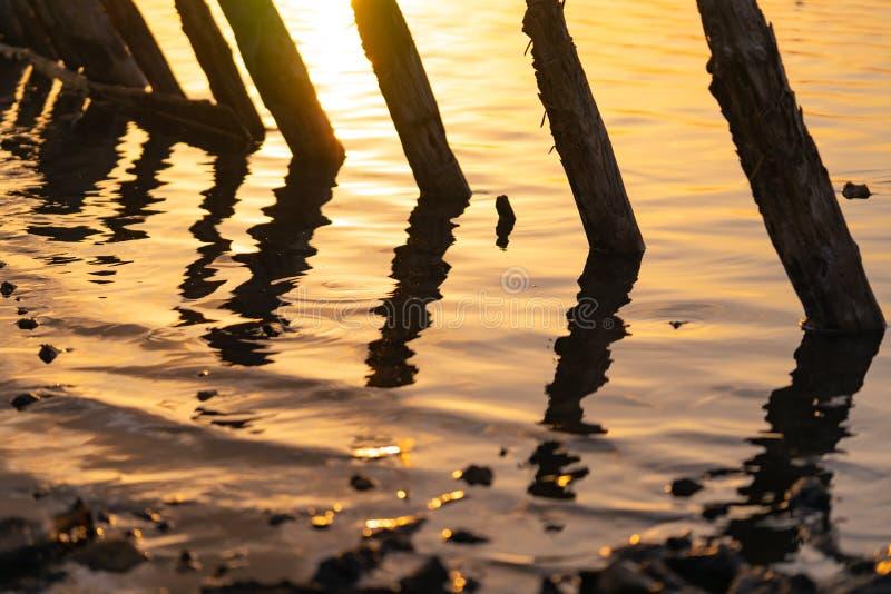 Sonnenuntergang auf dem Kuyalnik Liman odessa ukraine Alte Klotz sind vom wasser- die Überreste eines alten Piers sichtbar lizenzfreie stockfotografie