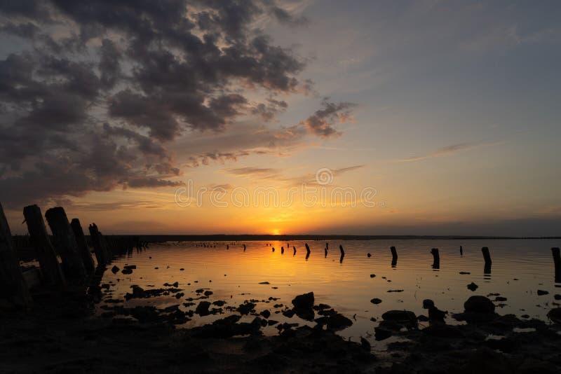 Sonnenuntergang auf dem Kuyalnik Liman odessa ukraine Alte Klotz sind vom wasser- die Überreste eines alten Piers sichtbar stockbilder
