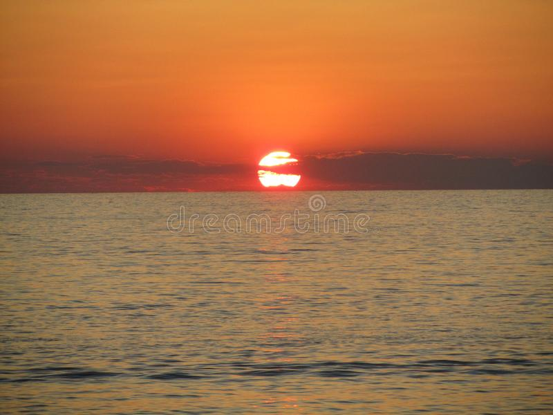 Sonnenuntergang auf dem Meer, Sonne in den Wolken glättend lizenzfreie stockbilder