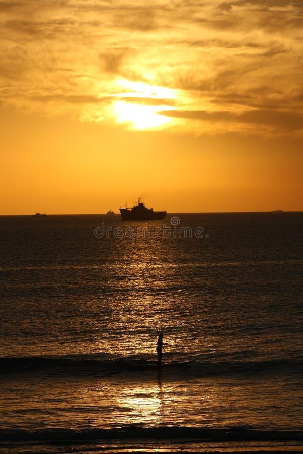 Sonnenuntergang auf dem Strand mit einem Schiff und einem Surfer stockfotografie