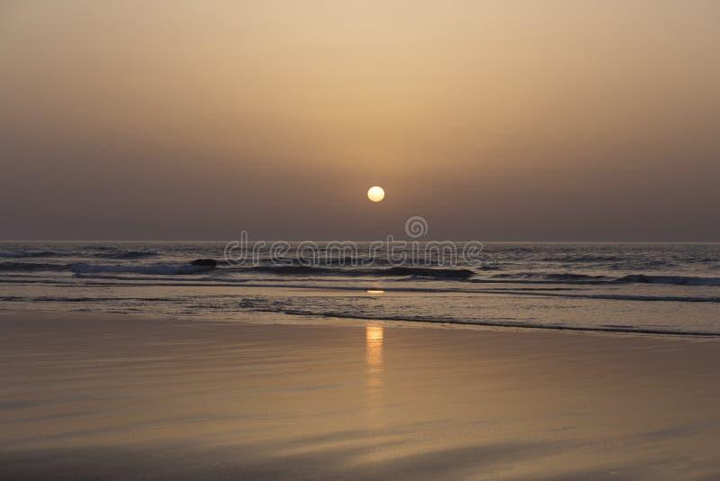 Sonnenuntergang auf dem Strand von Asilah in der Blaulandschaft orange Gelbs Marokkos stockfotografie