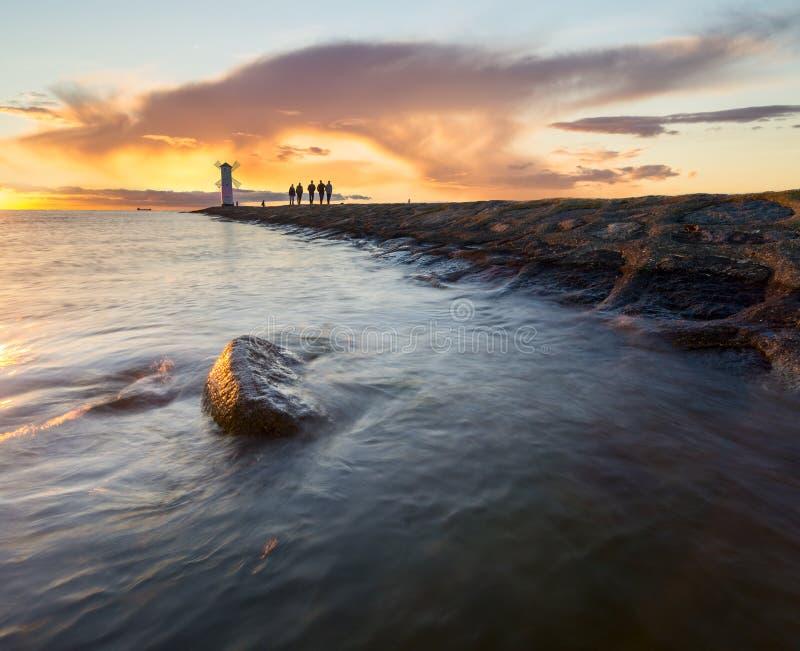 Sonnenuntergang auf der Küste, Leuchtturmwindmühle in Swinoujscie, Polen lizenzfreie stockbilder