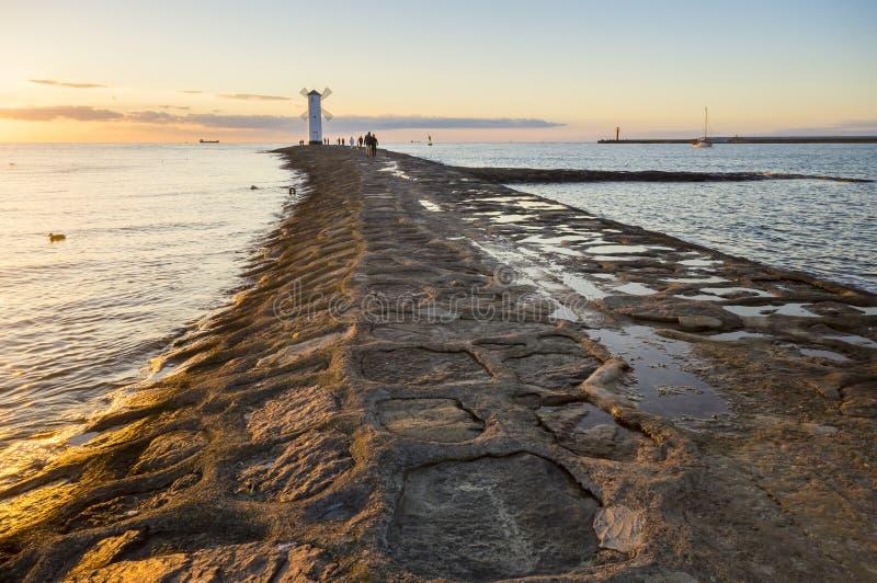 Sonnenuntergang auf der Küste, Leuchtturmwindmühle in Swinoujscie, Polen stockbild