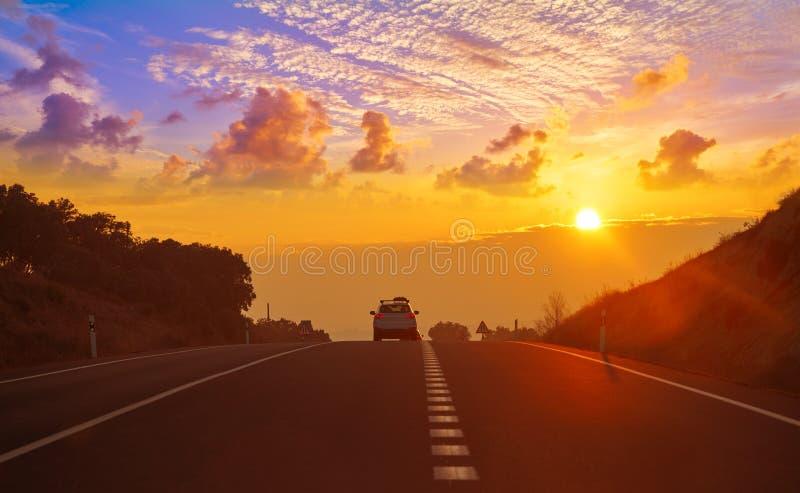 Sonnenuntergang auf der Straße mit goldenem Himmel stockbild