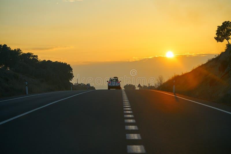 Sonnenuntergang auf der Straße mit goldenem Himmel lizenzfreie stockfotografie