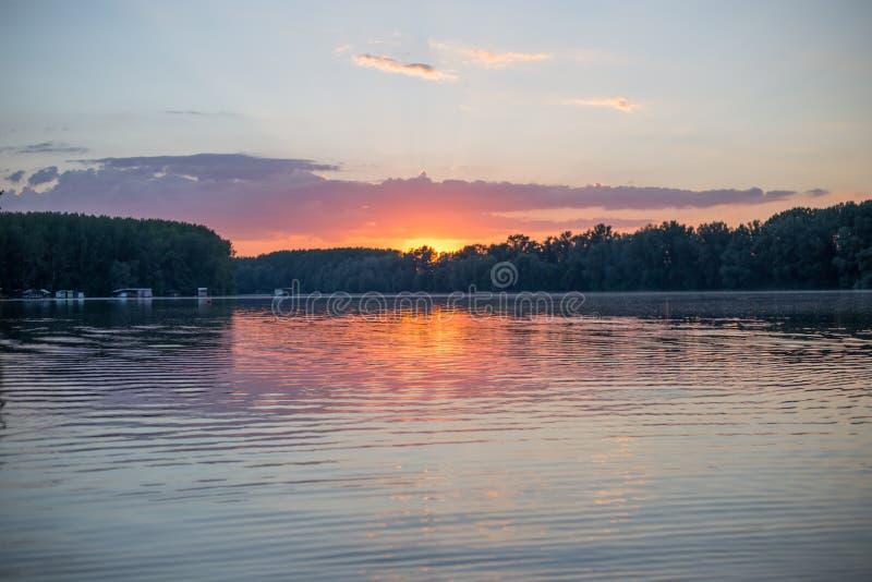 Sonnenuntergang auf einem See mit Häusern auf Wasser stockfoto