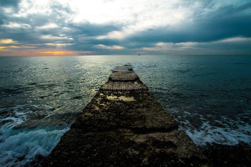 Sonnenuntergang auf einem Steinpier lizenzfreies stockfoto