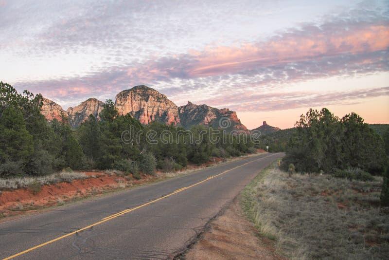 Sonnenuntergang auf Landstraße mit Ansicht von roten Felsformationen Sedona in Arizona, USA stockbild