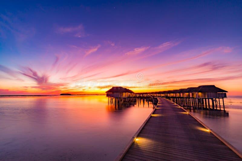 Sonnenuntergang auf Malediven-Insel, Luxuswasserlandhäuser nehmen und hölzerner Pier Zuflucht Schöner Himmel und Wolken und Stran lizenzfreies stockfoto