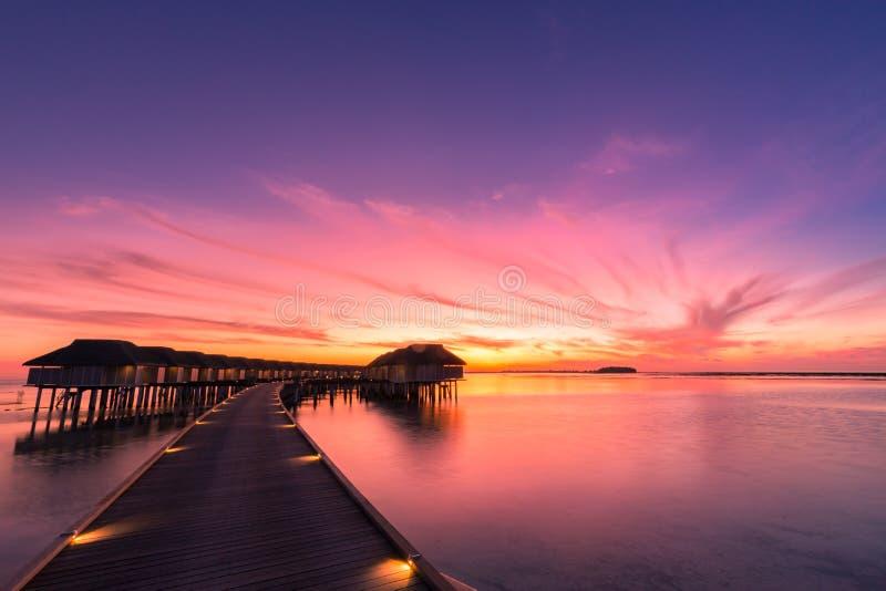 Sonnenuntergang auf Malediven-Insel, Luxuswasserlandhäuser nehmen und hölzerner Pier Zuflucht Schöner Himmel und Wolken und Stran stockbilder