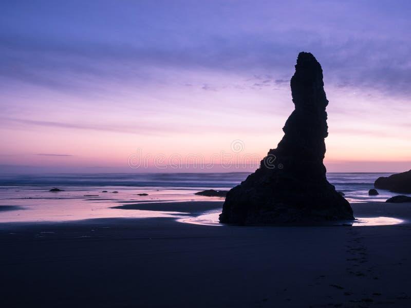 Sonnenuntergang auf Ozeanstrand mit Klippen stockfoto