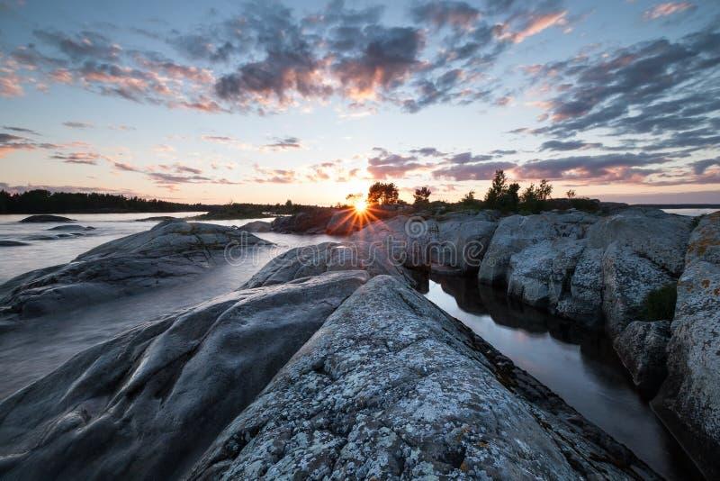 Sonnenuntergang auf See mit steiniger Küstenlandschaft stockfotos