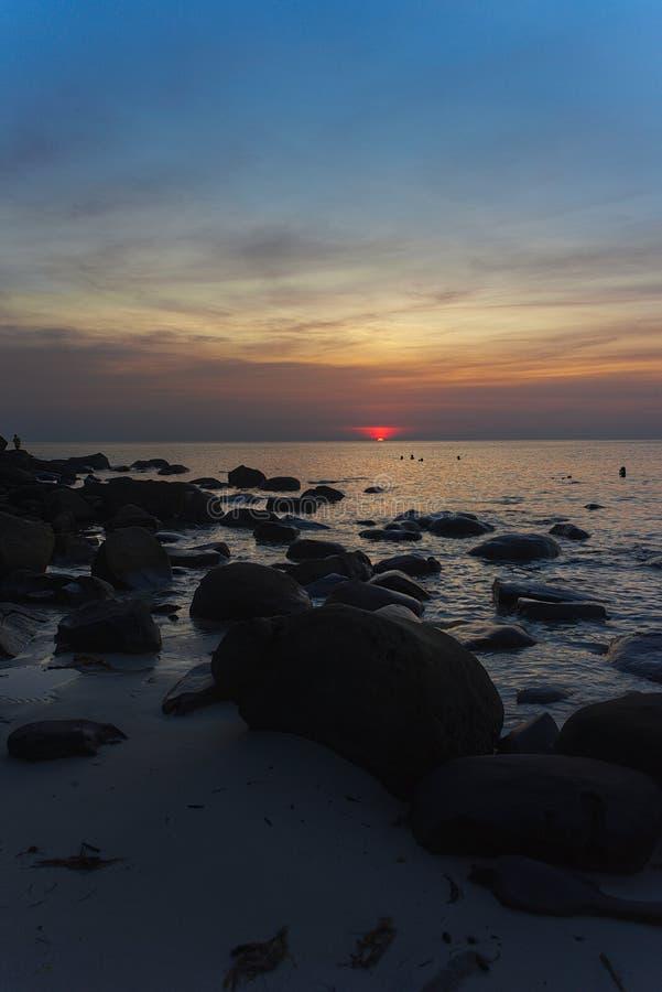 Sonnenuntergang auf Strand mit den Felsen stockbild