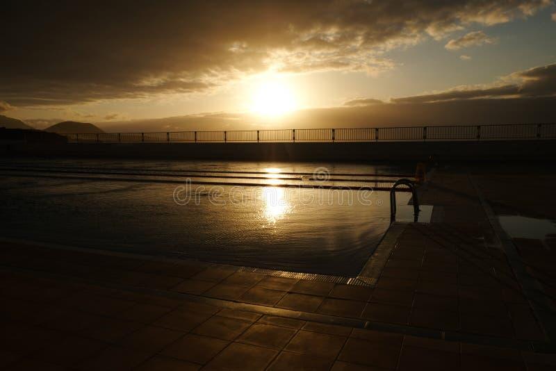 Sonnenuntergang ?ber Swimmingpool lizenzfreie stockbilder