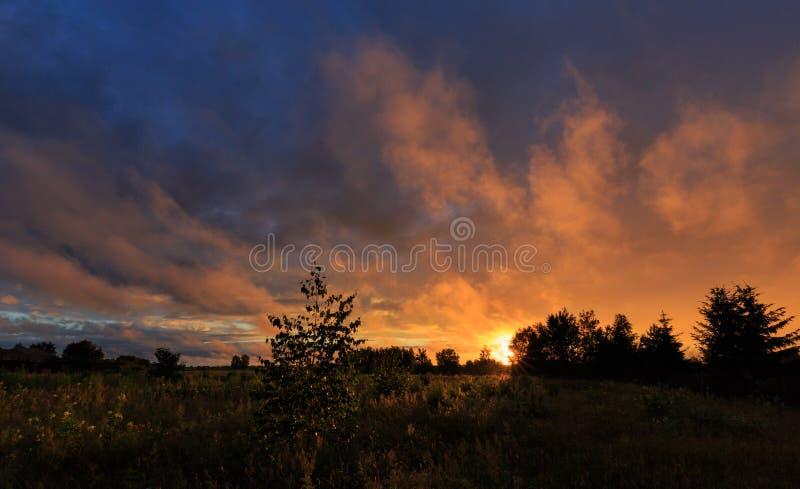 Sonnenuntergang bewölkt Regen nachher über Feld stockbild