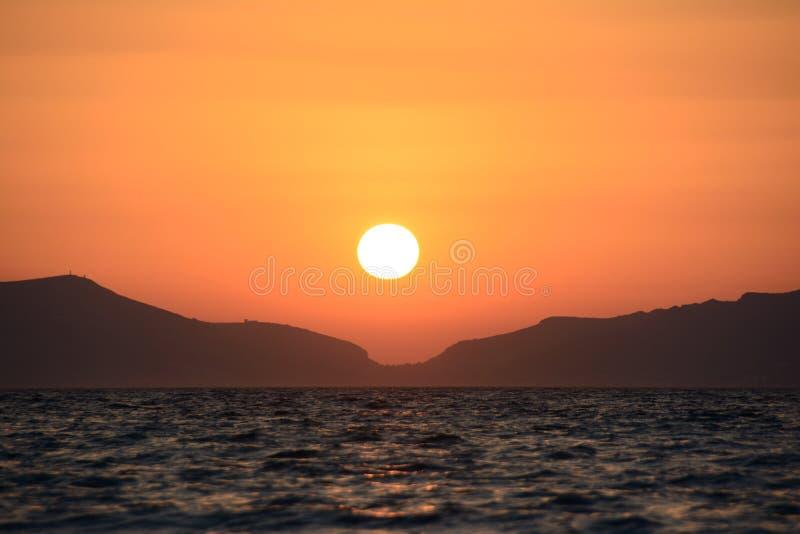 Sonnenuntergang in der Nähe von Bergen und Meer lizenzfreies stockbild