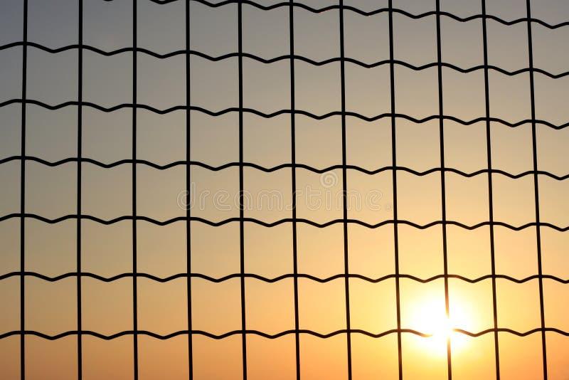 Sonnenuntergang durch einen Maschendraht stockfoto