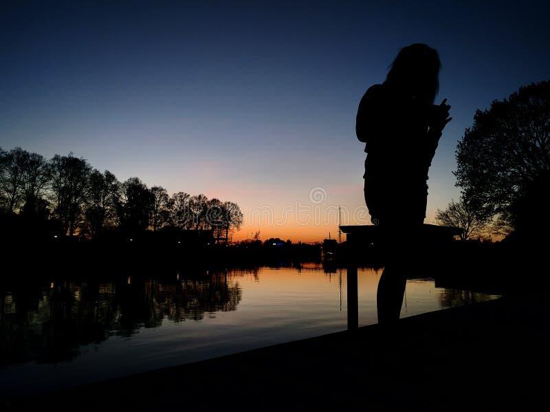 Sonnenuntergang durch Fluss lizenzfreies stockfoto
