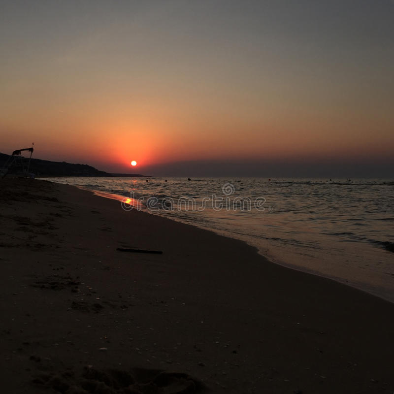 Sonnenuntergang durch Meer im Sommer lizenzfreies stockfoto