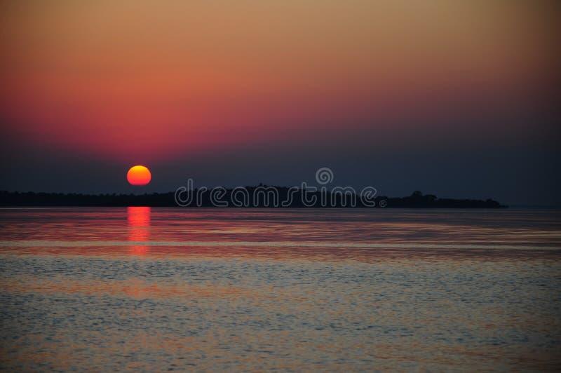 Sonnenuntergang durch Meer im Sommer stockbild