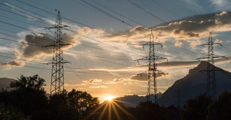 Sonnenuntergang in einer Berglandschaft mit Linien und Masten der elektrischen Leistung im Vordergrund lizenzfreies stockbild