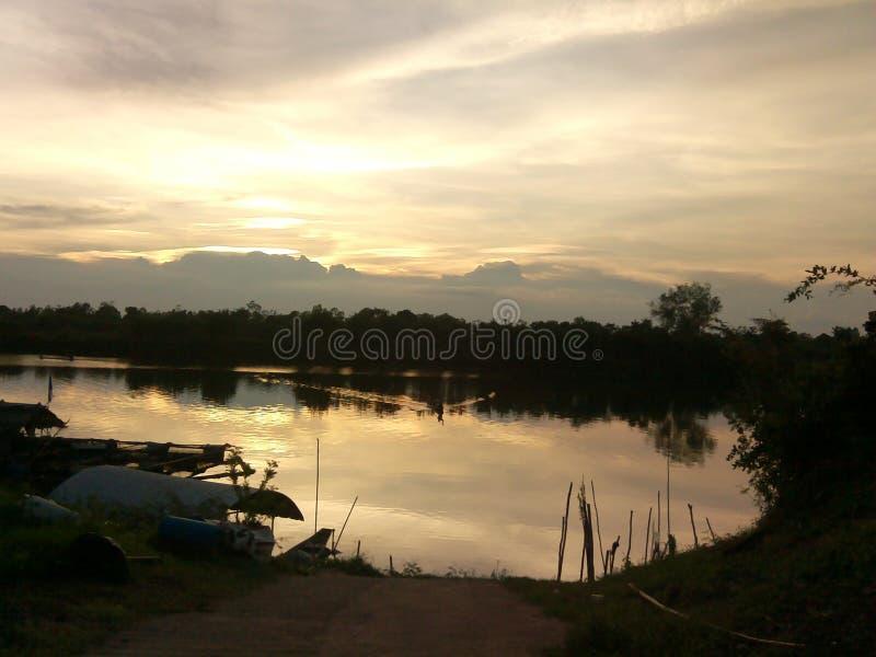 Sonnenuntergang am Flussufer lizenzfreie stockbilder