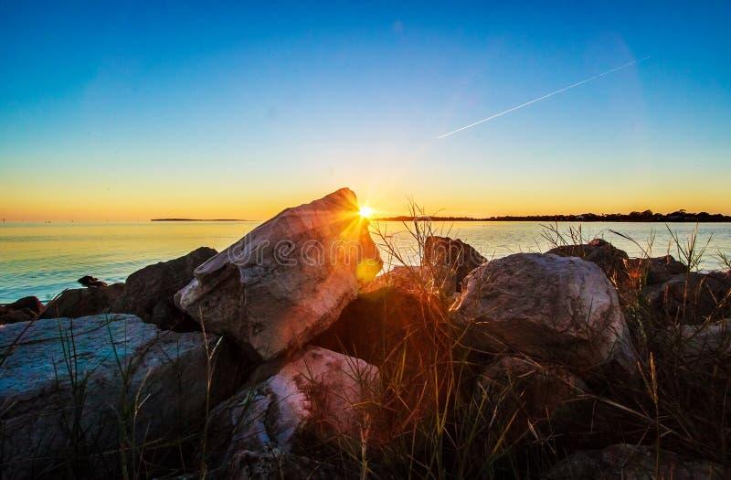 Sonnenuntergang hinter dem felsigen Stein stockfotografie