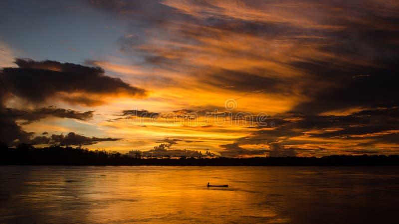 Sonnenuntergang hinter einem kleinen Boot beim Amazonas stockbilder