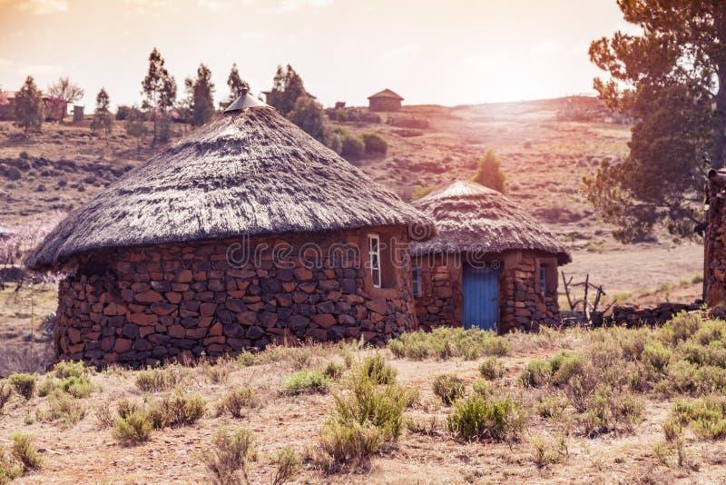 Sonnenuntergang hinter Lesotho-Hütten stockfotografie