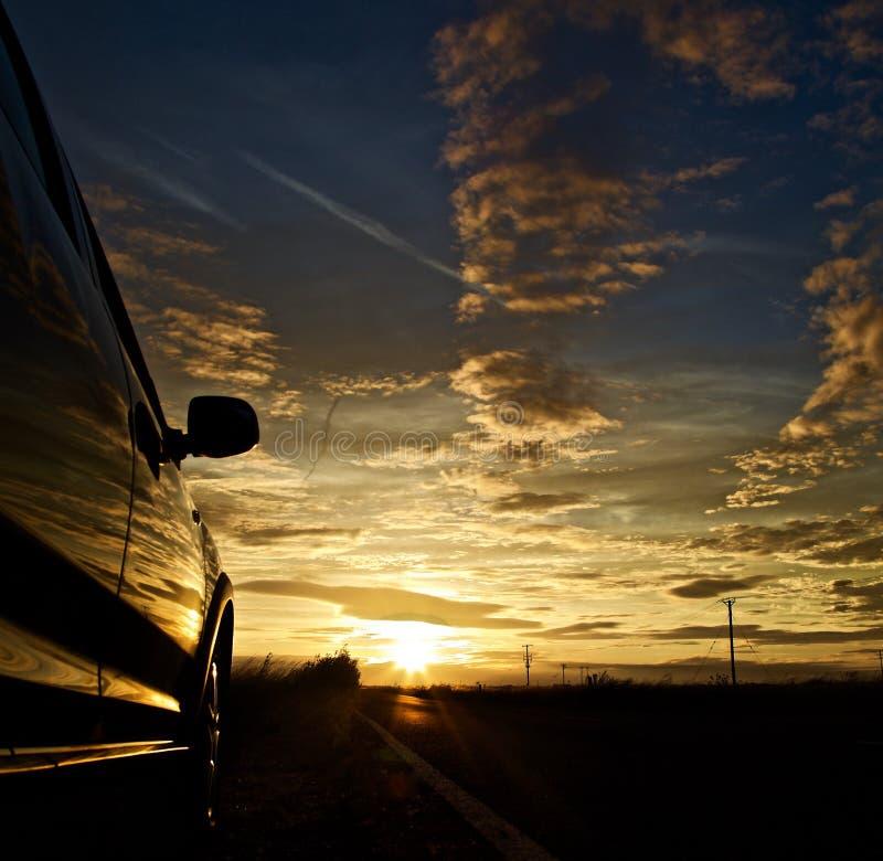 Sonnenuntergang im entfernten mit einem parkendes Auto auf dem links lizenzfreie stockfotografie