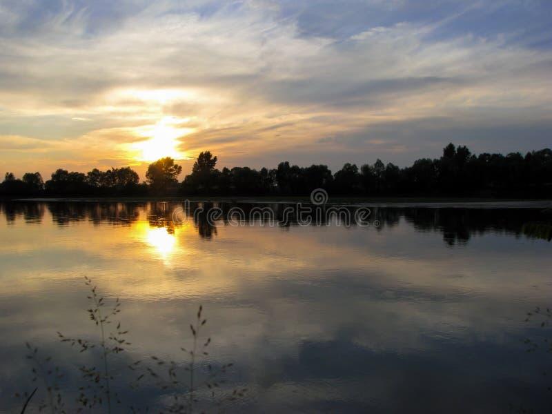 Sonnenuntergang im Fluss mit Reflex stockbilder