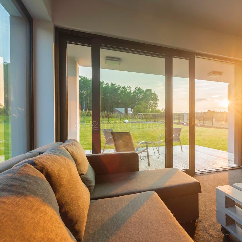 Sonnenuntergang im modernen Wohnzimmer lizenzfreies stockbild