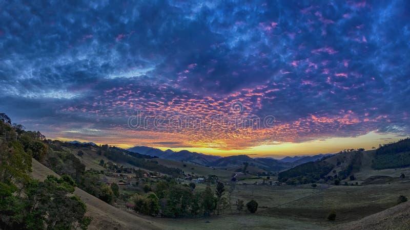 Sonnenuntergang im Tal zwischen Hügeln im Sao Bento tun Sapucai - Sao Paulo - Brasilien - Panoramafoto lizenzfreies stockfoto