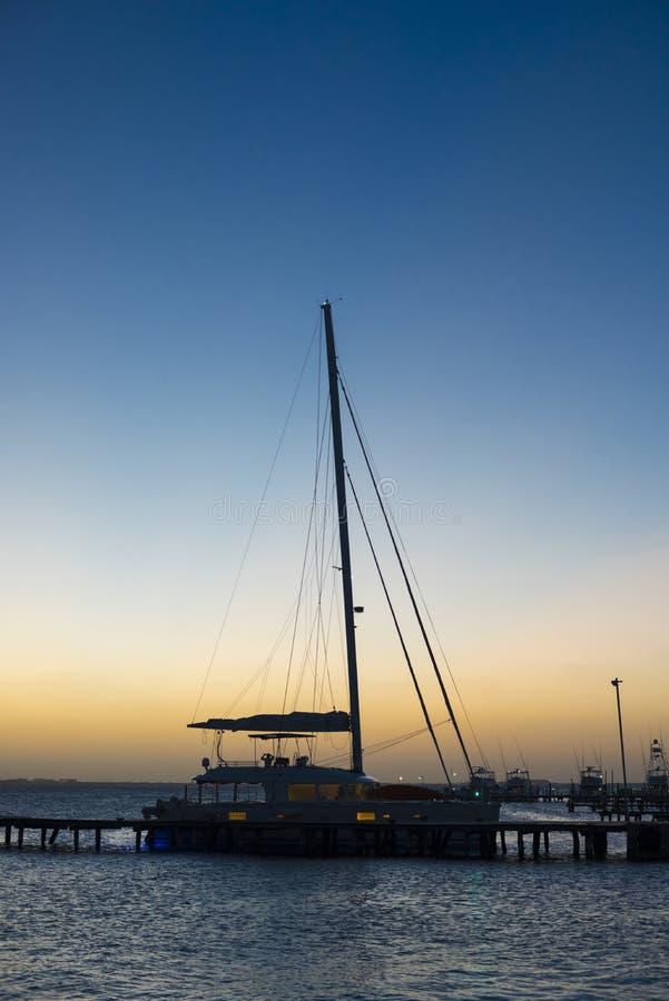 Sonnenuntergang am Jachthafen mit angekoppelter Yacht und ruhigem See lizenzfreie stockbilder
