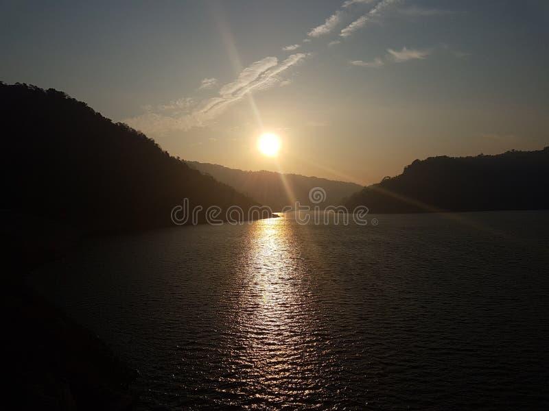 Sonnenuntergang mit der Sonne nachgedacht über das Wasser stockfotos