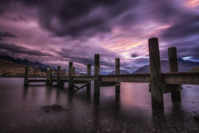 Sonnenuntergang mit einem Dock in See wakatipu stockfotografie