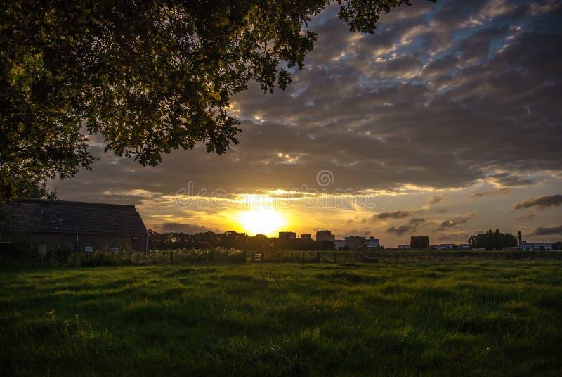 Sonnenuntergang mit einer Scheune und einer Wiese stockbild