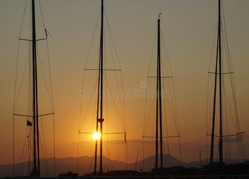 Sonnenuntergang mit Masten von Segelbooten in der Hintergrundbeleuchtung stockfotos