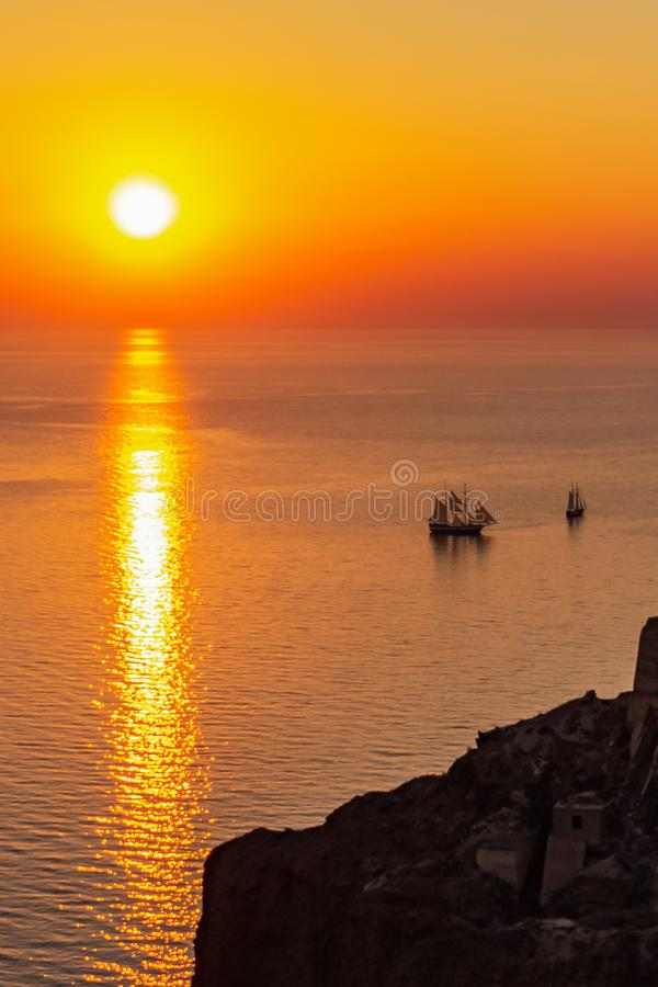 Sonnenuntergang mit Segelschiffen nahe Oia Santorini Griechenland lizenzfreie stockfotografie