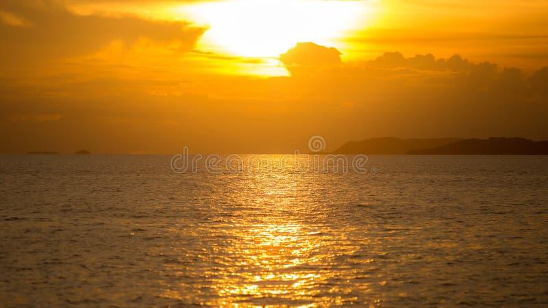 Sonnenuntergang mit Sonnenlicht über Meer oder Ozean mit orange oder goldenem Licht lizenzfreies stockbild