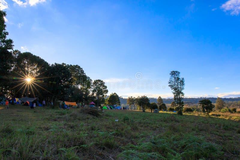 Sonnenuntergang mit Sonnenlichtsonnenstrahlen oder -Sonnenstrahlen an Nationalpark Thung Salaeng Luang, Leute sind Campingzelt lizenzfreie stockfotos