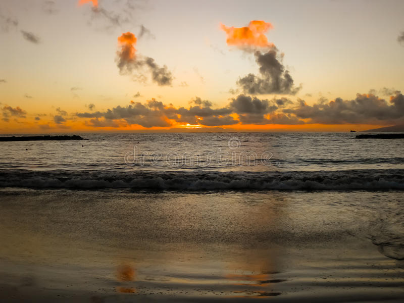 Sonnenuntergang mit Wolken durch den Ozean lizenzfreie stockfotos