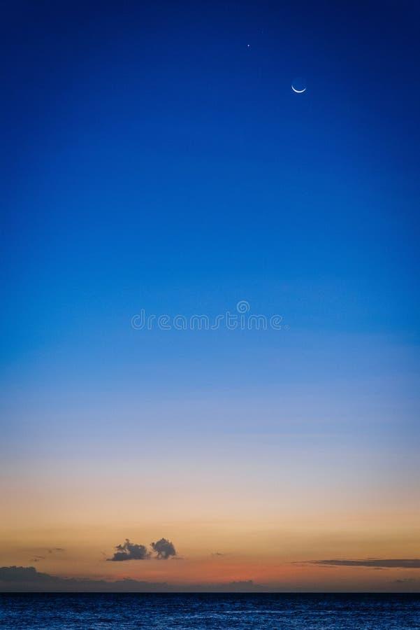 Sonnenuntergang Moonrise über dem Ozean stockfotos