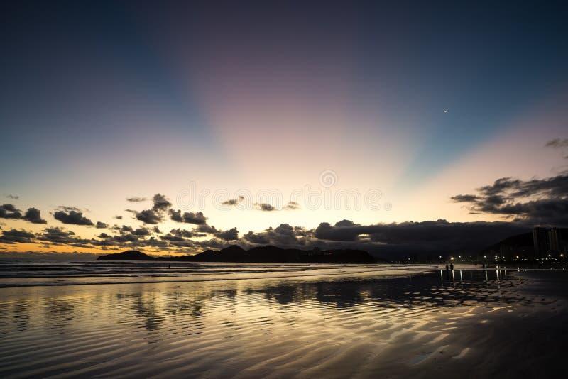 Sonnenuntergang in Santos mit rosa Strahlen und sichelförmigem Mond lizenzfreie stockfotografie