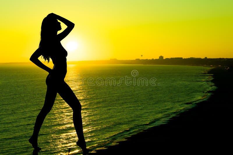Glückliche sorglose frau, die schönen sonnenuntergang auf