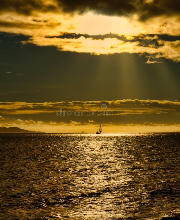 Sonnenuntergang-Sonnenstrahlen ?ber Yacht lizenzfreie stockfotos