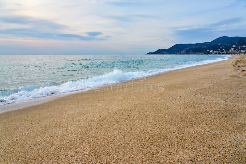 Sonnenuntergang am Strand, Wellen mit dem Schaum, der Sand schlägt lizenzfreies stockbild