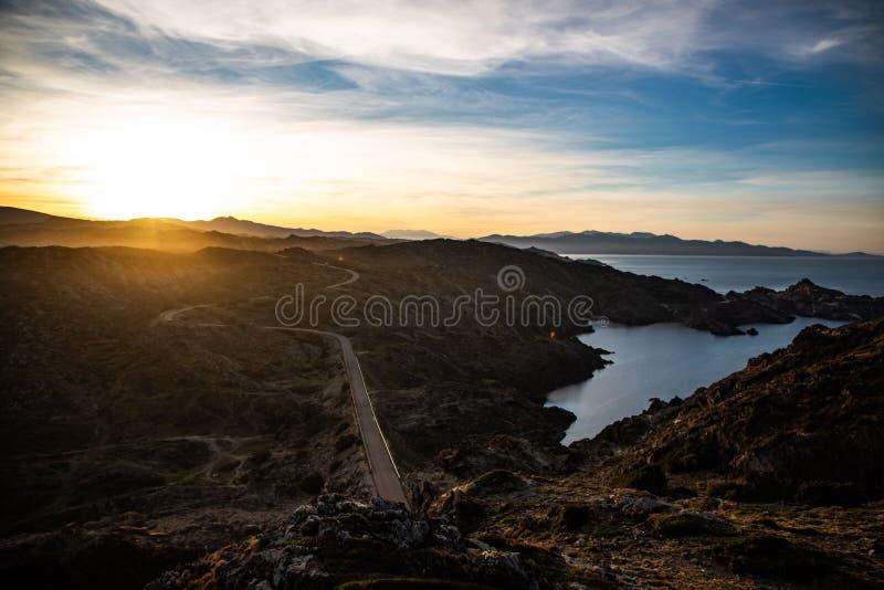 Sonnenuntergang und eine gebogene Straßenansicht in Cap de Creus, Catalunya lizenzfreies stockbild