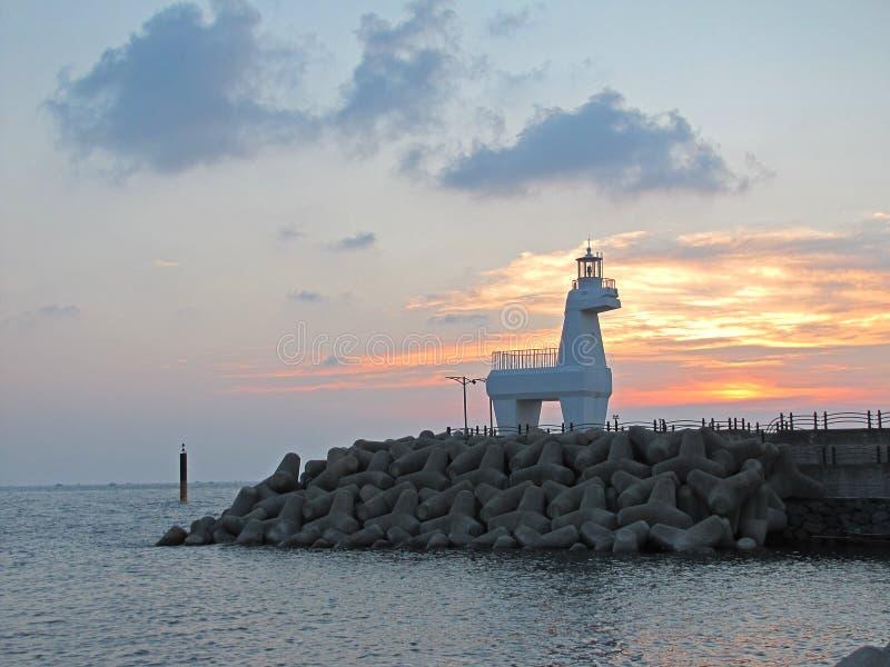 Sonnenuntergang und Leuchtturm in Form des Pferds auf Jeju-Insel in Südkorea lizenzfreie stockbilder