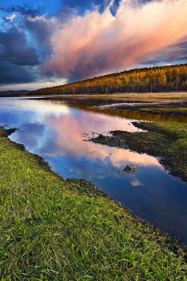 Sonnenuntergang unter dem See und dem Wald lizenzfreie stockbilder
